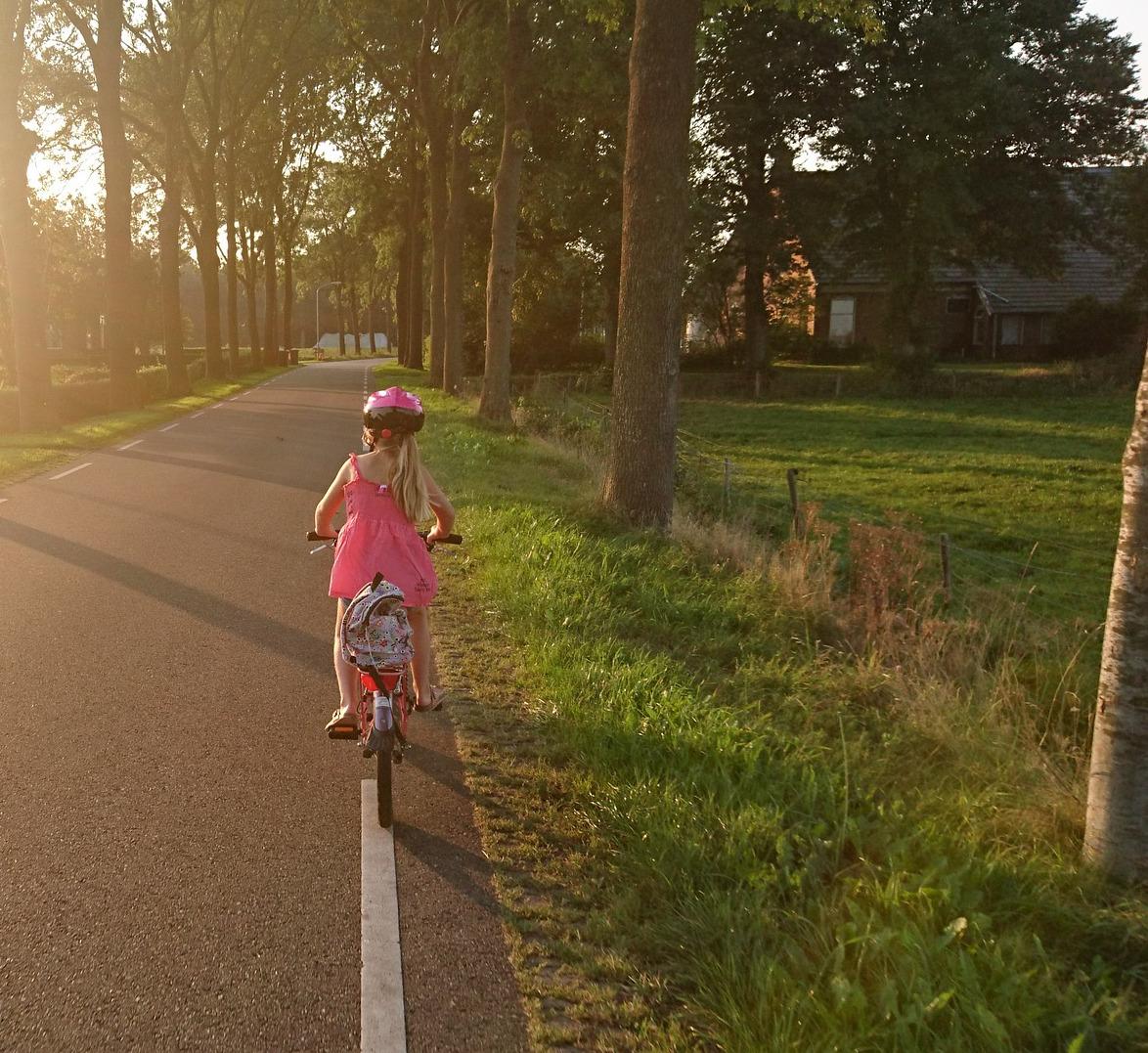 Kind auf Fahrrad auf dem Weg zur Schule im Straßenverkehr